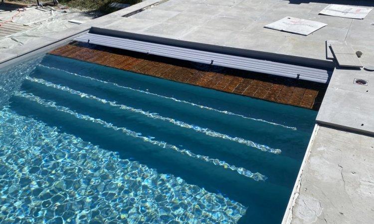 Piscine8.75M X 4M, PVC gris clair, skimmer extra plat gris clair, escalier pleine largeur, volet immergé avec caillebotis immergé en IPE